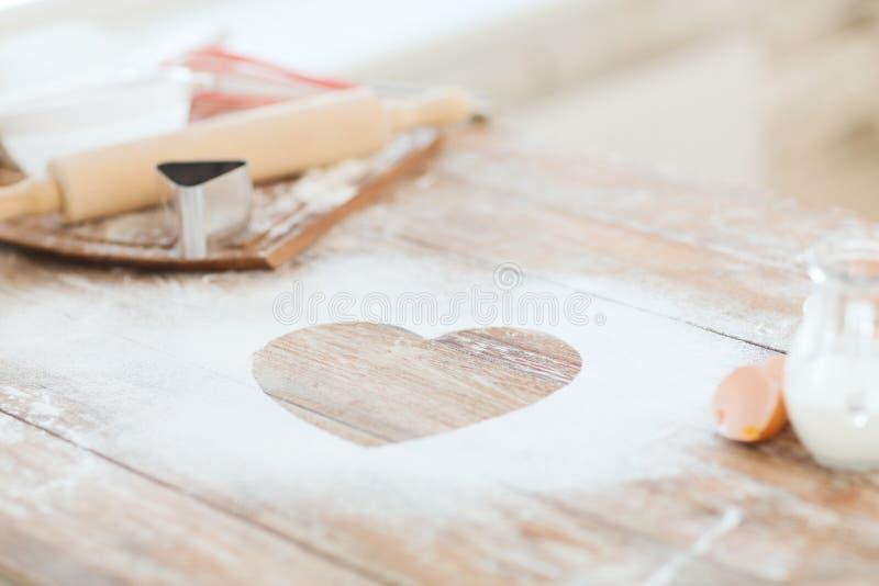 Закройте вверх сердца муки на деревянном столе дома стоковая фотография rf