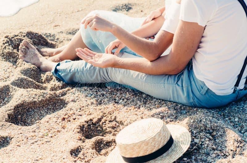 Закройте вверх сидеть пар сидя на песке на пляже Концепция влюбленности лета Праздник ослабляя, каникулы пляжа стоковое изображение rf