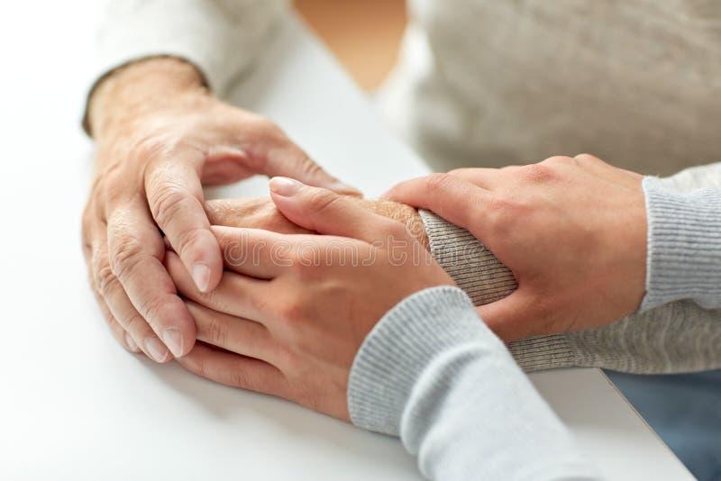 Закройте вверх старика и молодой женщины держа руки стоковое фото