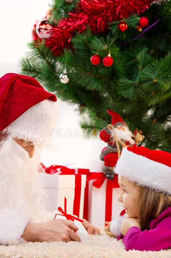 Закройте вверх старого Санта Клауса давая малый настоящий момент к маленькой девочке стоковое фото