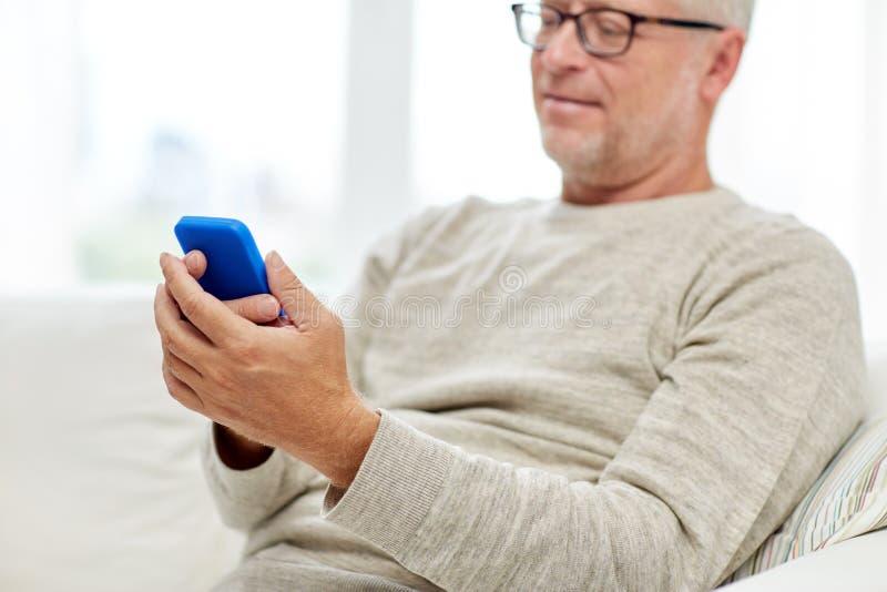 Закройте вверх старшего человека с smartphone дома стоковое фото rf