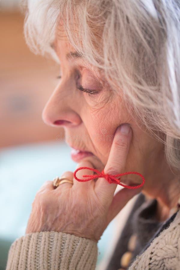 Закройте вверх старшей женщины при строка связанная вокруг пальца как Remin стоковое изображение