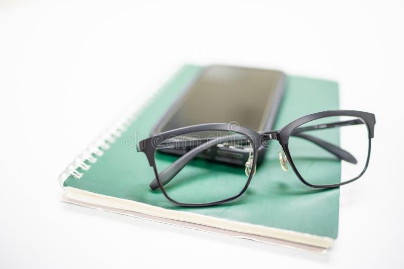 Закройте вверх стекел чтения на мобильном смартфоне и зеленой тетради на белой таблице Технология образования и концепция работы стоковые изображения rf