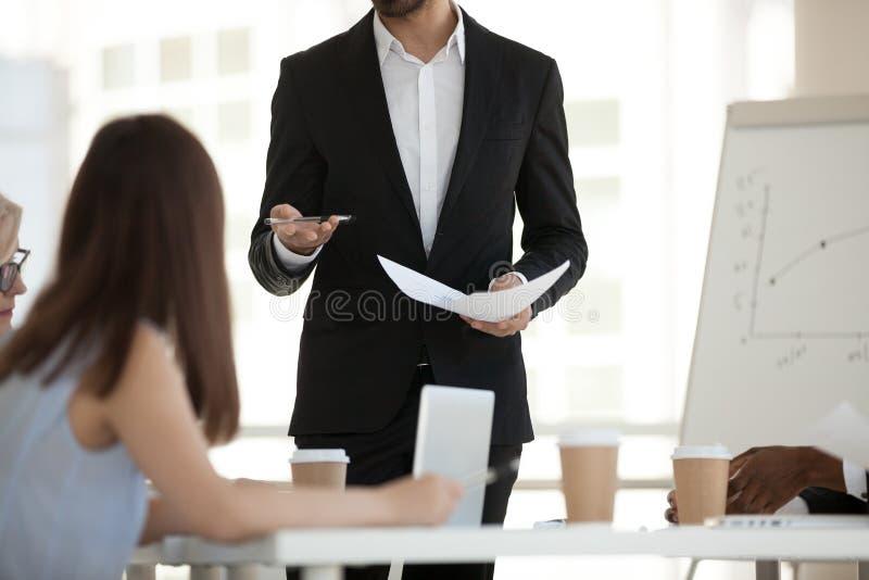 Закройте вверх стойки бизнесмена на брифинге разговаривая с работниками стоковые фотографии rf