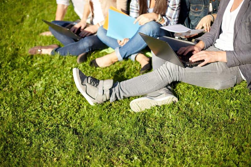 Закройте вверх студентов при компьтер-книжка сидя на траве стоковые изображения rf