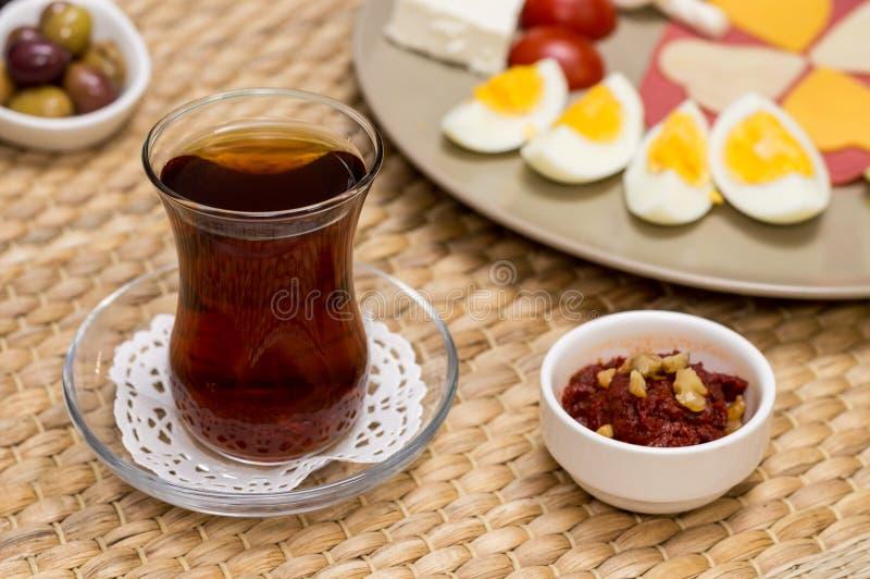 Закройте вверх традиционных турецких чая и закуски с запачканным взглядом завтрака с сыром, салями, вареным яйцом, и томатом стоковые изображения rf