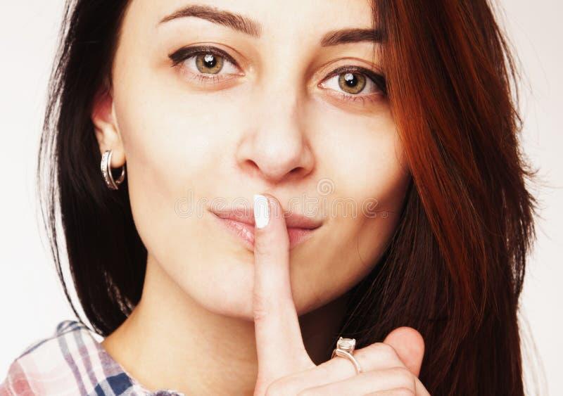 Закройте вверх угодите! - Палец на губах Привлекательная женщина со знаком стоковые изображения