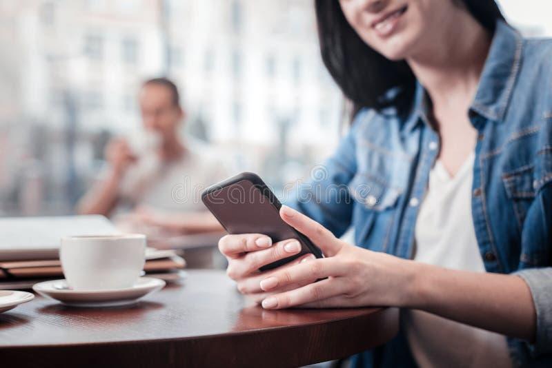 Закройте вверх усмехаясь девушки которая используя ее телефон стоковая фотография rf