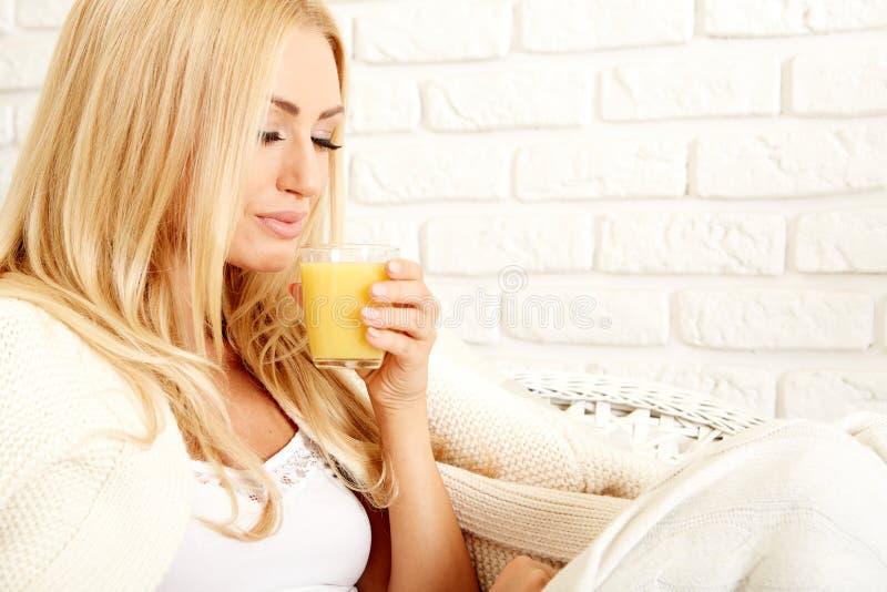 Закройте вверх усмехаясь женщины с апельсиновым соком стоковое фото