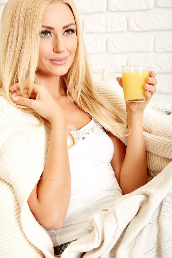 Закройте вверх усмехаясь женщины с апельсиновым соком стоковая фотография