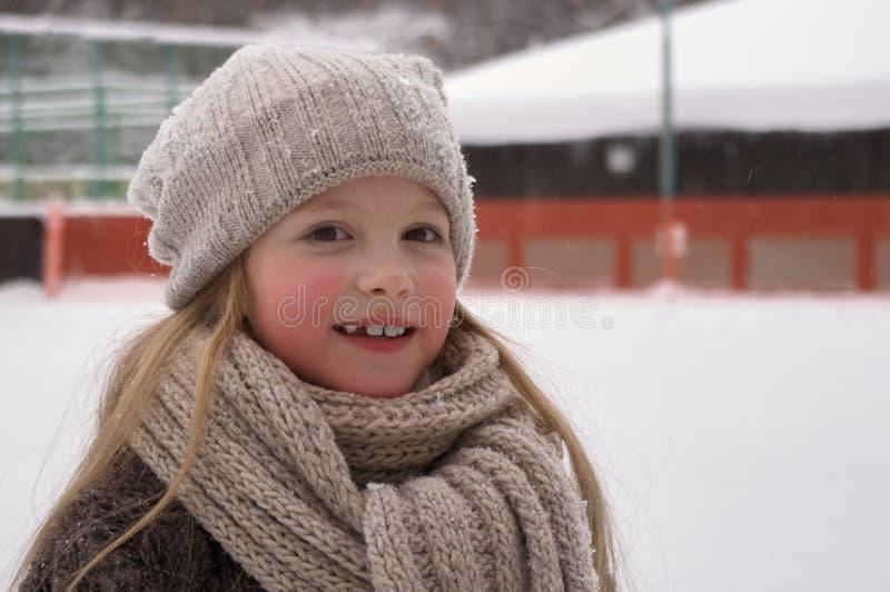 Закройте вверх усмехаясь милой девушки со шляпой связанной зимой На открытом воздухе съемка с несосредоточенной запачканной предп стоковые фото