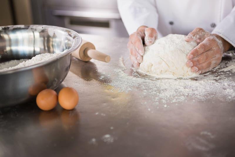 Закройте вверх хлебопека подготавливая тесто стоковое фото