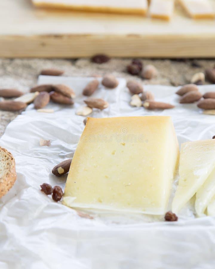 Закройте вверх частей сыра и зажаренных в духовке миндалин на каменной таблице стоковые изображения