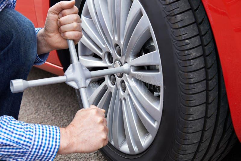 Закройте вверх человека с колесом автомобиля утюга покрышки изменяя стоковые фотографии rf