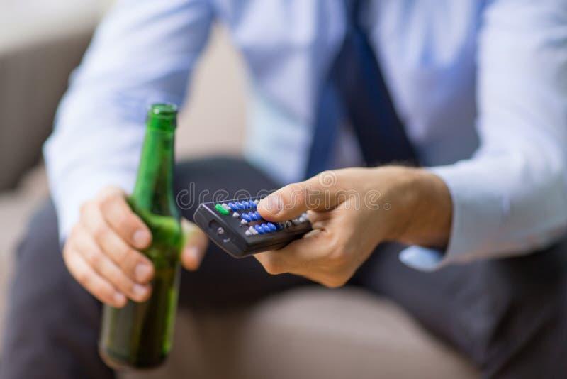 Закройте вверх человека с пивом ТВ удаленным выпивая стоковые фото