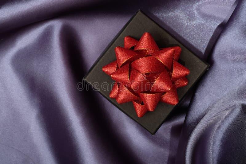 Закройте вверх черной подарочной коробки на темной ткани стоковое фото rf