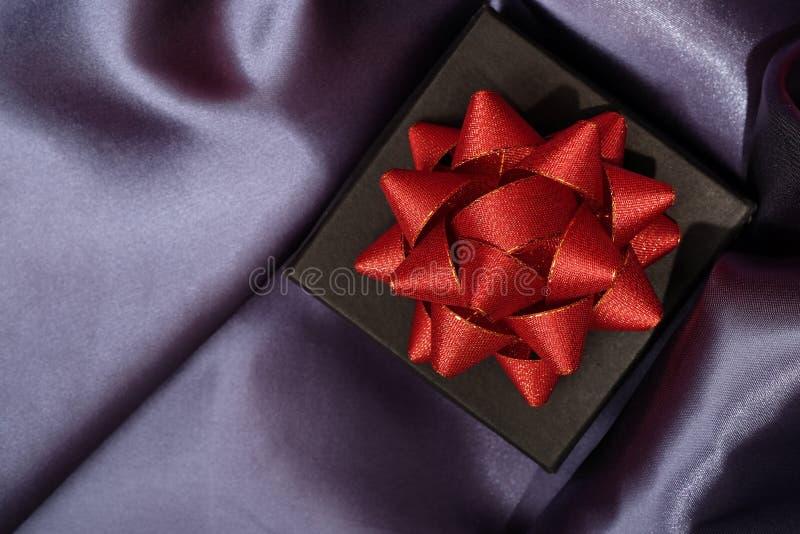 Закройте вверх черной подарочной коробки на темной ткани стоковая фотография rf