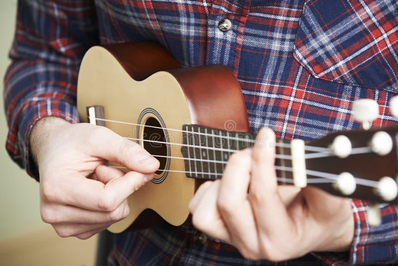 Закройте вверх человека играя гавайскую гитару стоковые фотографии rf