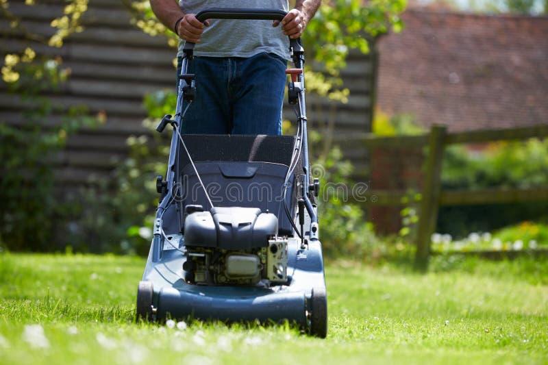 Закройте вверх человека работая в траве вырезывания сада с косилкой стоковое изображение rf