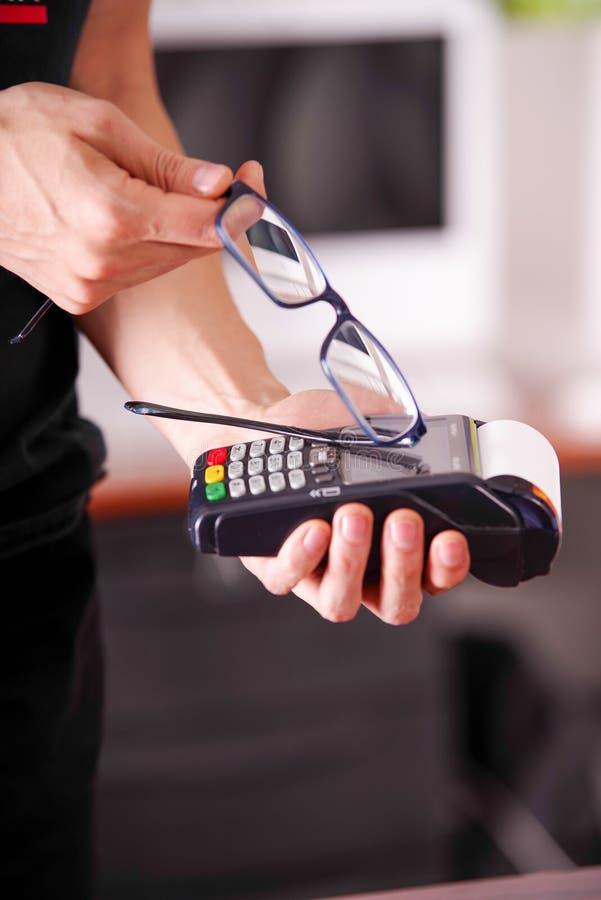 Закройте вверх человека руки держа современную оплату с новой технологией оплат используя умные стекла, купите и продайте стоковое фото rf