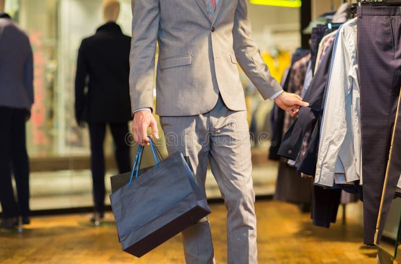 Закройте вверх человека с хозяйственными сумками на магазине стоковые изображения rf