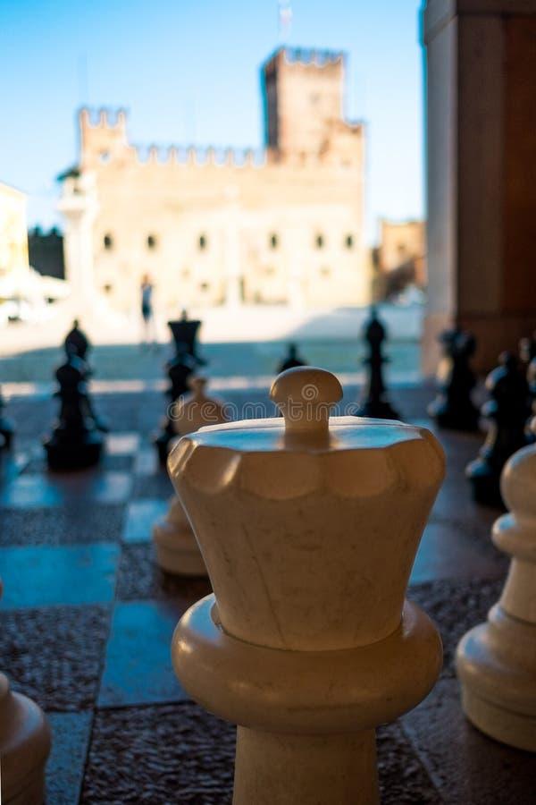 Закройте вверх шахматной фигуры в старом средневековом итальянском городке Marostica в области венето со средневековыми замком и  стоковая фотография rf