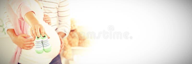 Закройте вверх яркой беременной женщины держа ботинки младенца пока супруг касаясь ее животу в комнате стоковая фотография rf