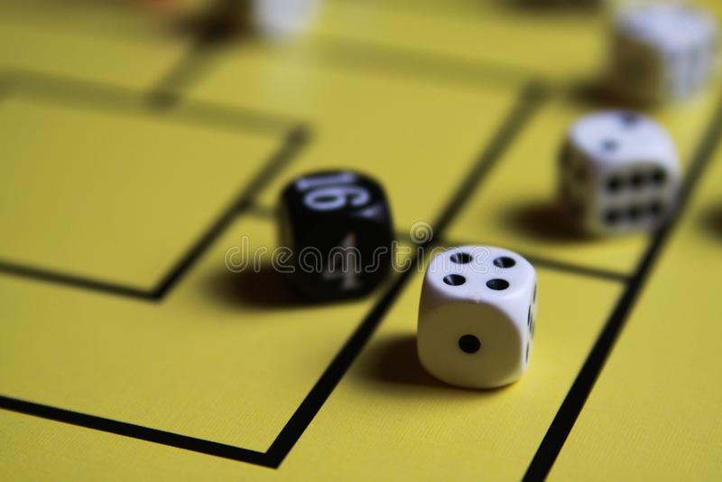 Закройте вверх dices на желтой доске игры стоковая фотография