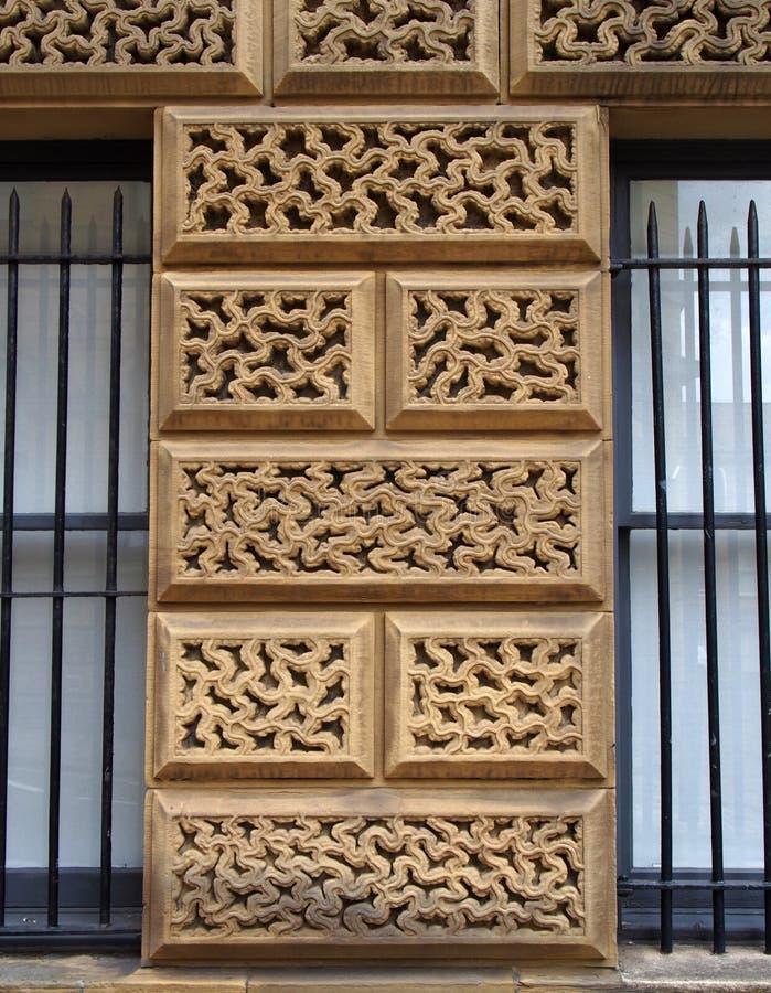 Закройте вверх ornately высекаенных больших каменных блоков на старом здании окруженном окнами со стальными прутами стоковое фото rf
