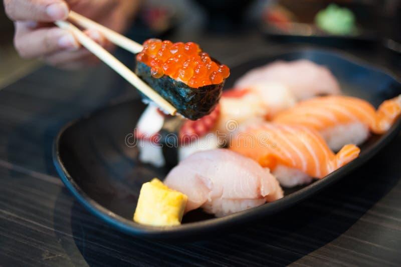 Закройте вверх suhi Ikura в палочках и комплекте суш разнообразия стоковая фотография rf