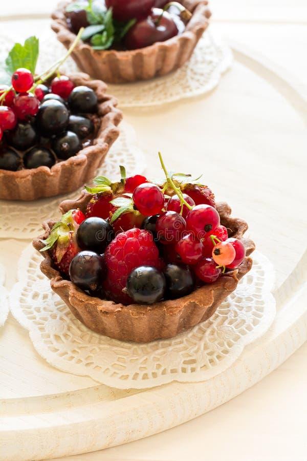 Закройте вверх tartlets шоколада с сливк шоколада, свежими клубниками, полениками, голубиками, красными смородинами и вишнями стоковые изображения rf