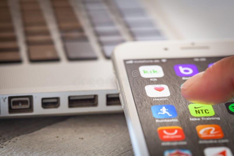 Закройте до пальца раскрывая здоровье app Яблока на экране iPhone 7 стоковая фотография