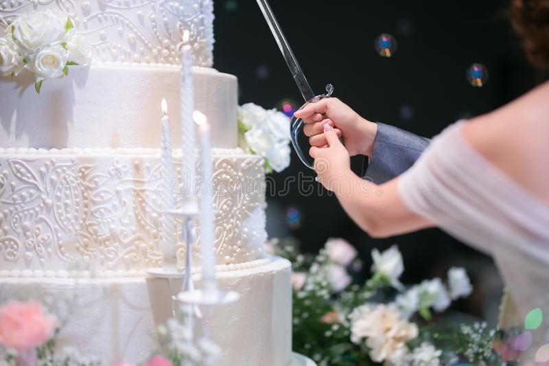Закройте до части тела жениха и невеста режьте их свадебный пирог стоковое изображение