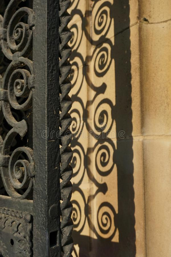 Закрученная в спираль чугунная дверь перил с тенью стоковые фотографии rf