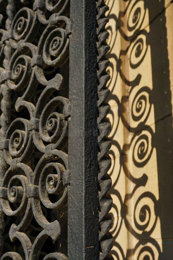 Закрученная в спираль чугунная дверь перил с тенью стоковое изображение rf