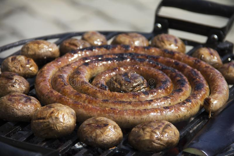 Закрученная круглая сосиска зажарила на барбекю стоковые изображения rf