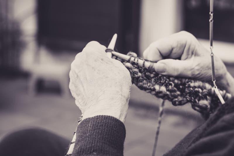 закрыв руки старухи на вязание стоковые фото