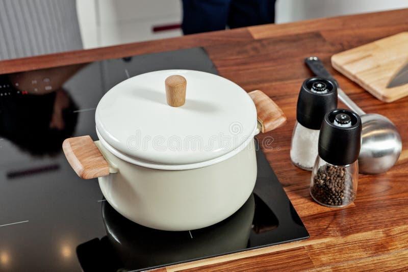 Закрытая белая кастрюлька с деревянными ручками на черной плите и стеклянными мельницами специи с papper и соль на деревянной таб стоковое фото rf