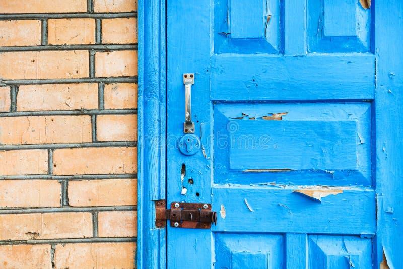 Закрытая затрапезная голубая деревянная дверь в кирпичной стене стоковые изображения