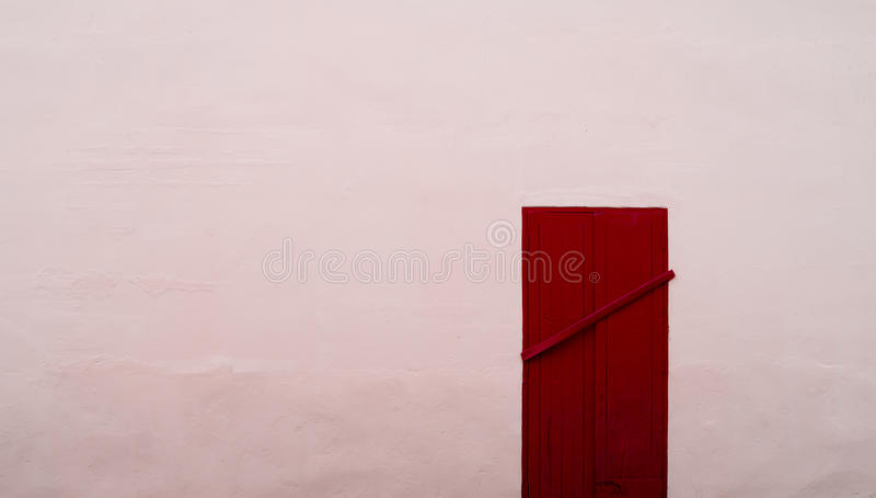 Закрытая постоянно красная деревянная дверь на розовой бетонной стене стоковое фото rf