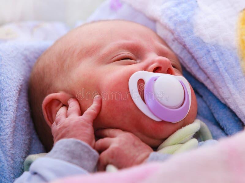 Закрытие маленького новорожденного, спящего со ситом во рту стоковая фотография