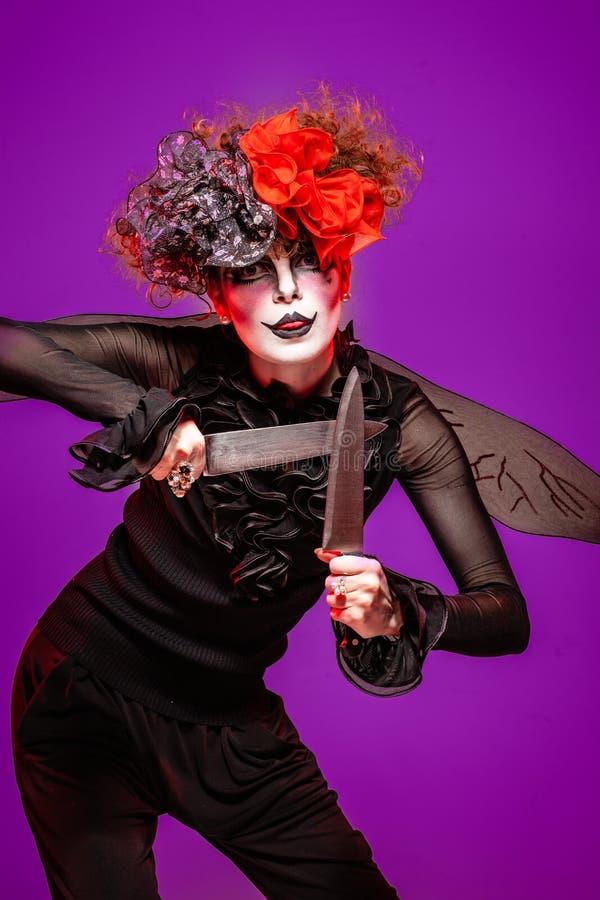 Закрытие страшной клоунской женщины-холдинга стоковое фото