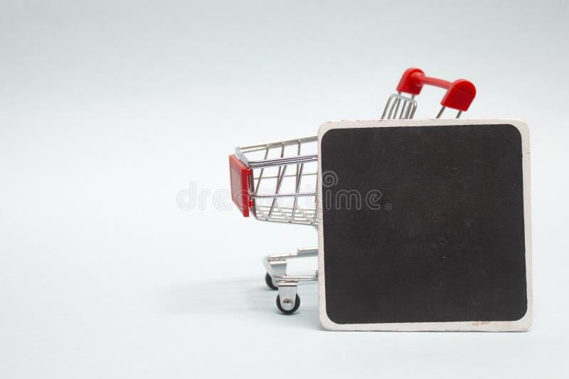 Закрытие торговой троллей с черной доской Mock-up на светлом фоне стоковые фото