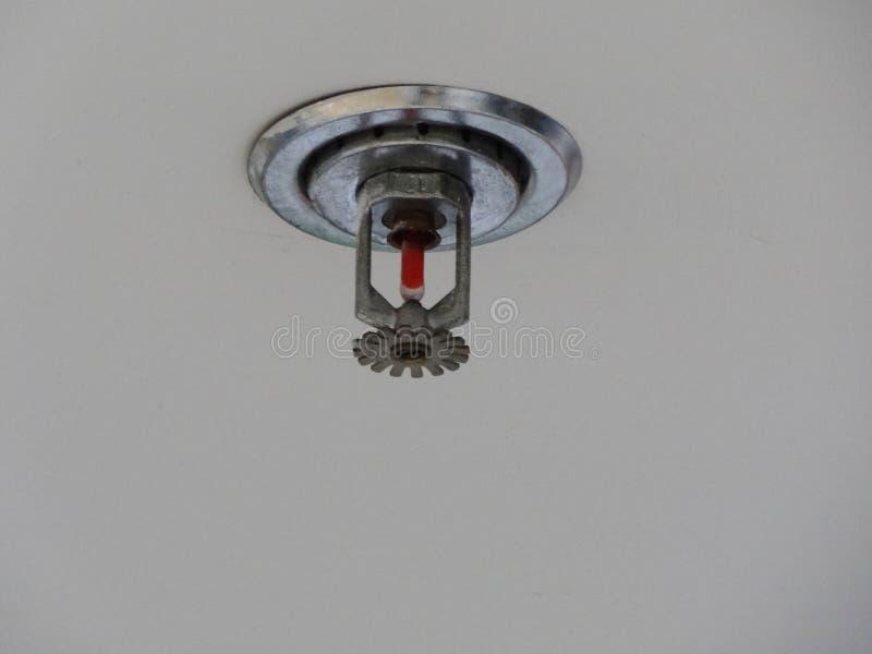 Закрытие установки пожарного спринклера на высоком белом потолке стоковое изображение rf