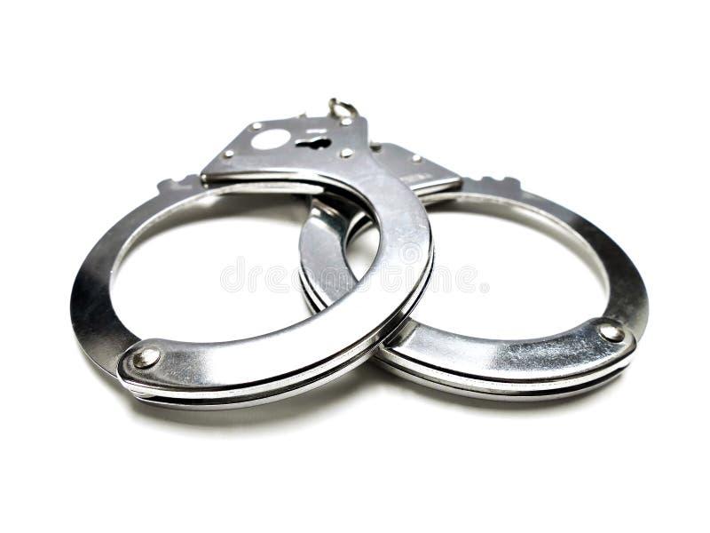 Закрытые наручники закрывают вверх на белой предпосылке стоковое фото