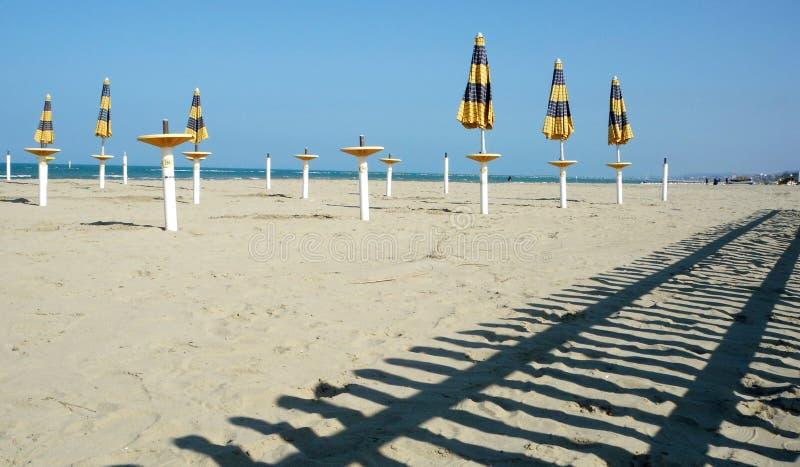 Закрытые парасоль и тень на пляже стоковое изображение rf