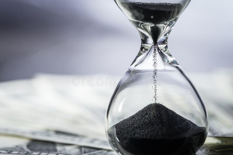 Закрытый вверх песка падая в sandglass или часы на долларе США стоковая фотография rf