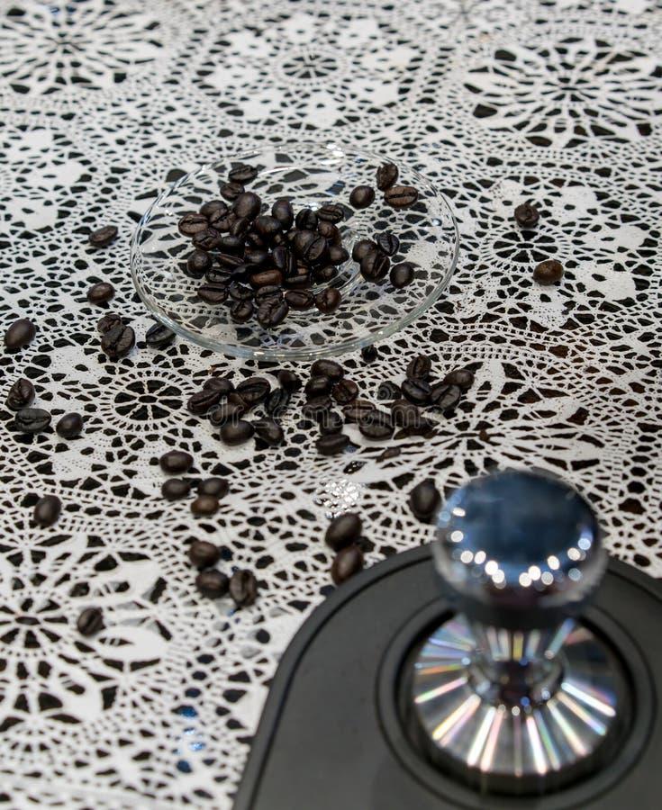 Закрытый вверх по кофейным зернам Arabica разбросал в стеклянный поддонник на croc стоковое фото