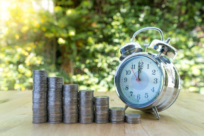 Закрытый вверх по съемке будильника с стогами монетки на зеленой предпосылке стоковое изображение rf