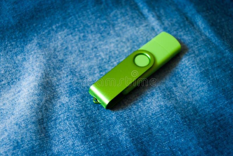 Закрытый привод вспышки USB зеленого цвета на предпосылке джинсов стоковое изображение rf
